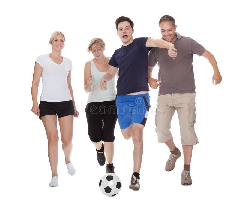 Aktiv familj som spelar fotboll arkivfoto