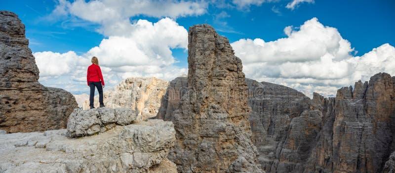 Aktiv fotvandrare som fotvandrar och att tycka om sikten som ser Dolomitesberglandskap arkivbild