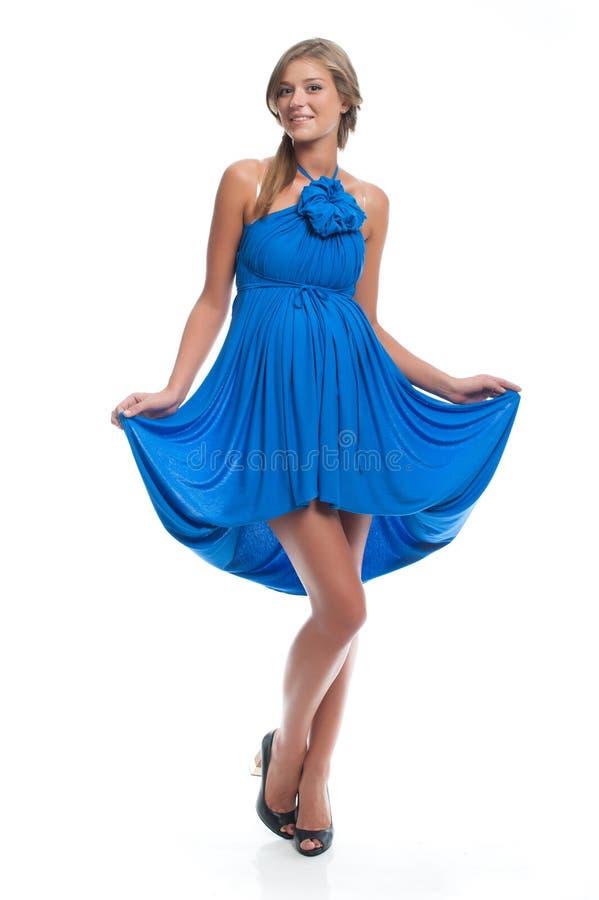 Aktiv härlig gravid modell i en blå klänning som är sarafan på en vit bakgrund Kläder för havandeskap arkivbilder