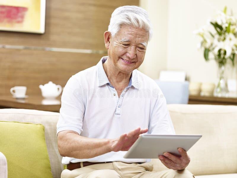 Aktiv hög asiatisk man som använder minnestavladatoren royaltyfri foto