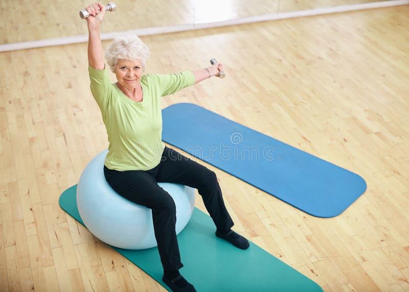 Aktiv hög kvinna på idrottshallen som övar med vikter arkivfoto
