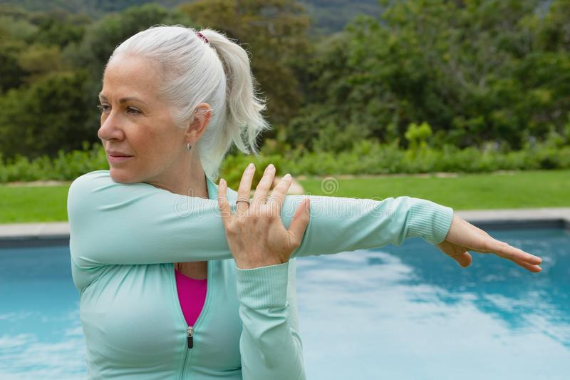 Aktiv hög kvinna som övar nära poolside i trädgården arkivbild