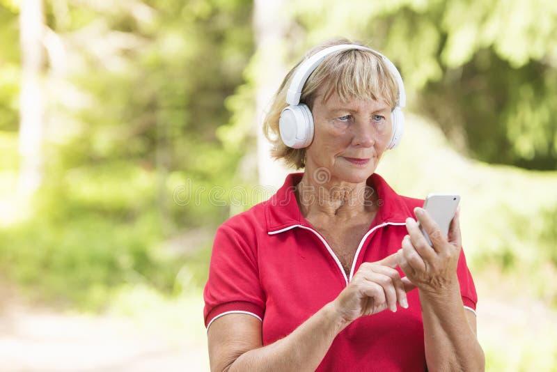 Aktiv hög kvinna som använder sporten spårande app royaltyfri foto