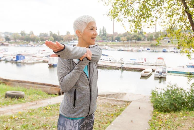 Aktiv hög kvinna som gör konditionövning arkivbild
