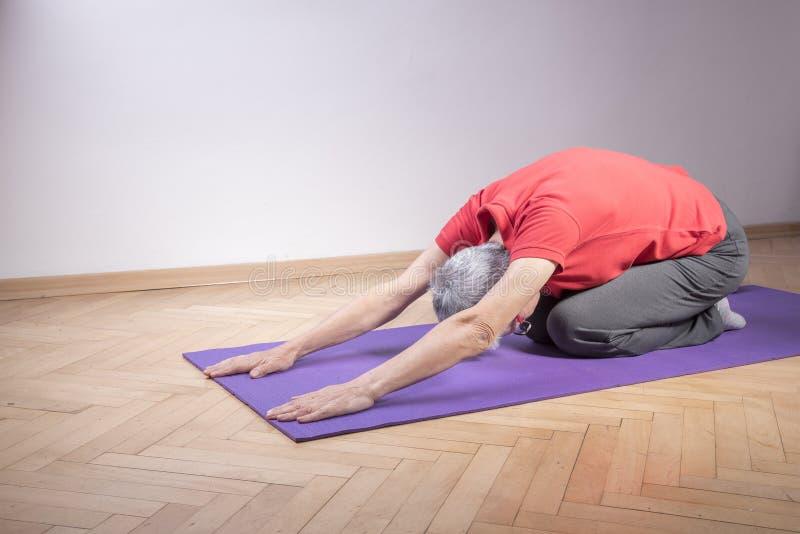 Aktiv hög kvinna som gör yoga royaltyfria bilder