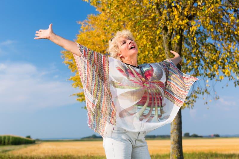 Aktiv hög kvinna som känner sig fri och lycklig, medan stå outdoo royaltyfria bilder