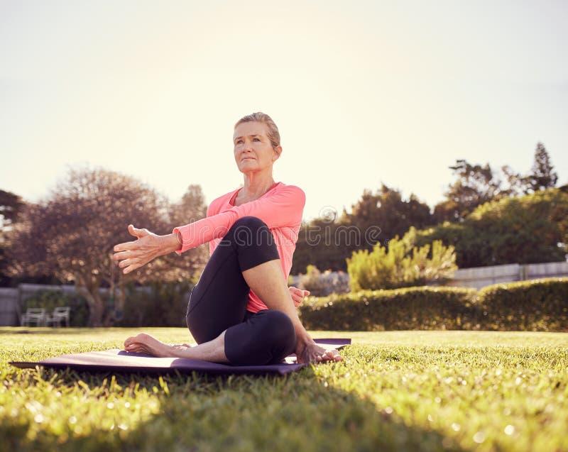 Aktiv hög kvinna som utomhus gör en yogavridning royaltyfri bild