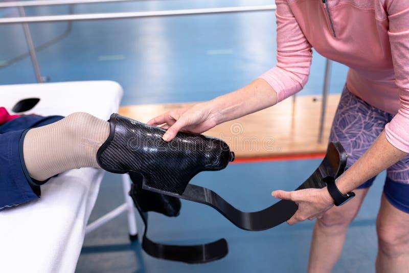 Aktiv hög kvinnlig instruktör som bär det prosthetic benet till den rörelsehindrade mannen i sportmitt arkivbild