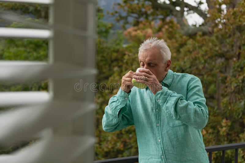Aktiv hög man som dricker kaffe på balkongen royaltyfria bilder