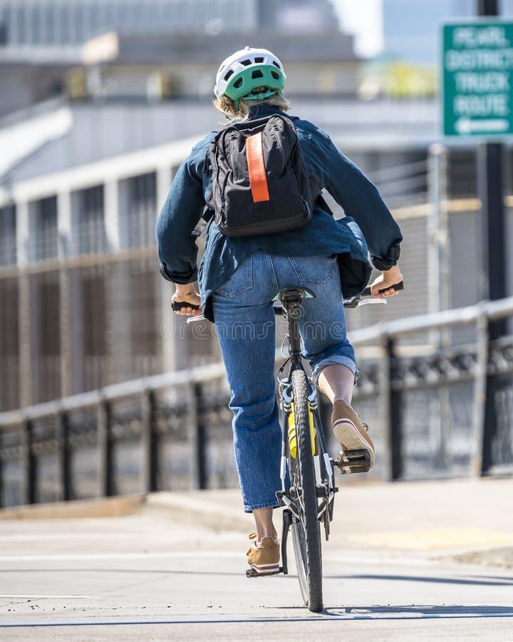 Aktiv kvinna med ryggsäckridningcykeln ner stadsgatan fotografering för bildbyråer
