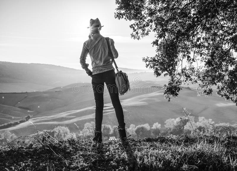 Aktiv kvinnafotvandrare i hatt med påsen som tycker om solnedgång i Tuscany royaltyfri foto
