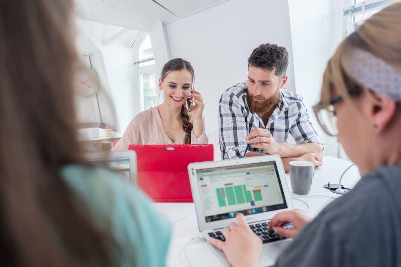 Aktiv kvinnlig entreprenör som in talar på mobil på ett delat skrivbord arkivfoto