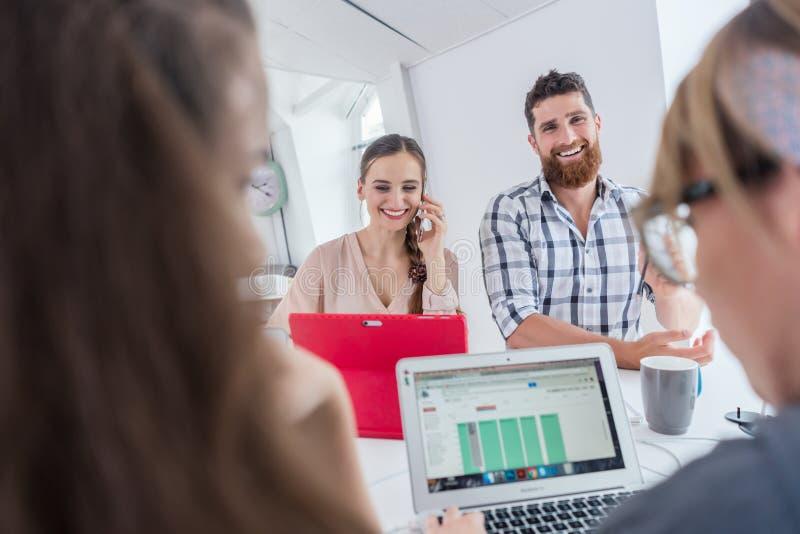 Aktiv kvinnlig entreprenör som talar på mobil på ett delat skrivbord royaltyfria bilder