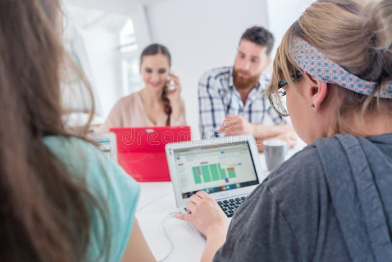 Aktiv kvinnlig entreprenör som talar på mobil på ett delat skrivbord arkivfoton