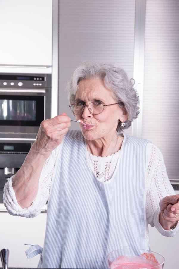 Aktiv kvinnlig pensionär i kök arkivfoton