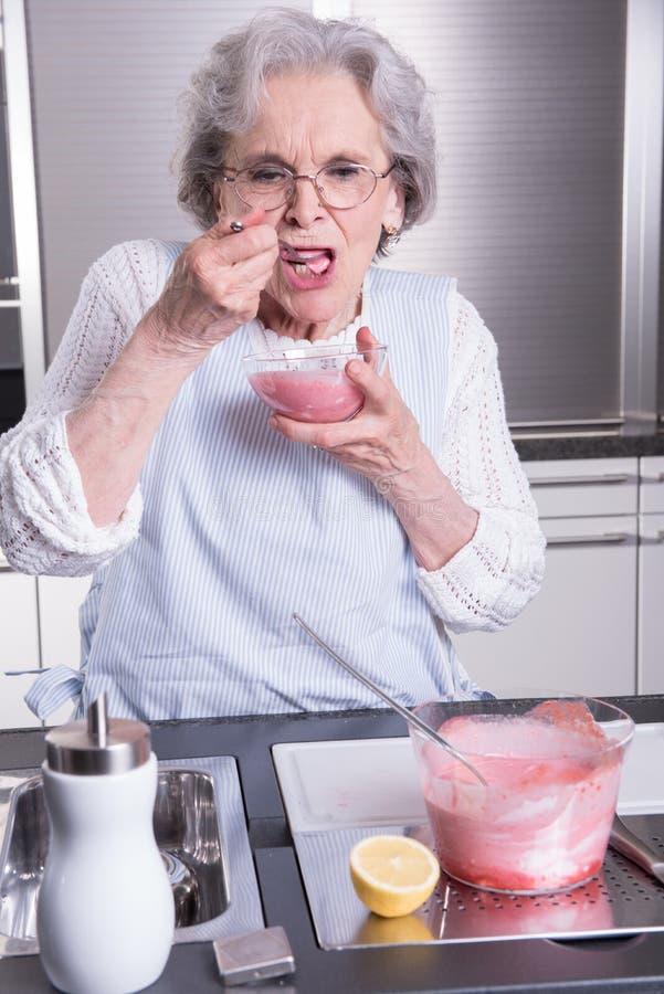 Aktiv kvinnlig pensionär i kök fotografering för bildbyråer