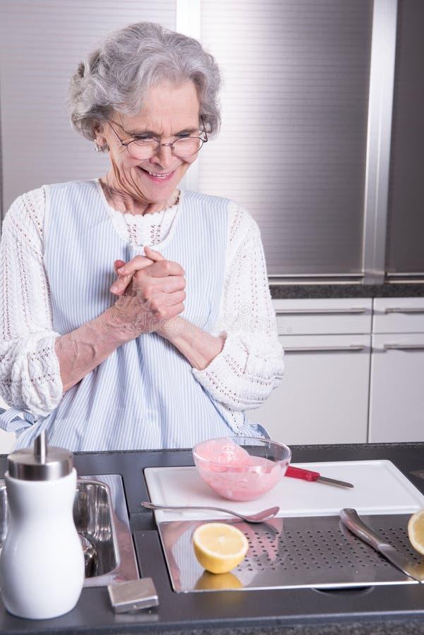 Aktiv kvinnlig pensionär i kök royaltyfri bild