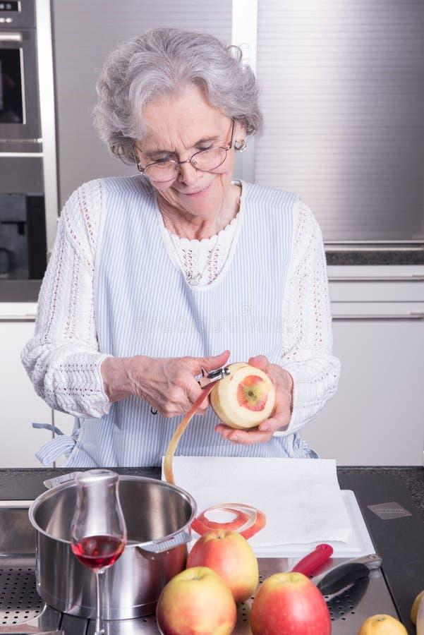 Aktiv kvinnlig pensionär i kök royaltyfri foto