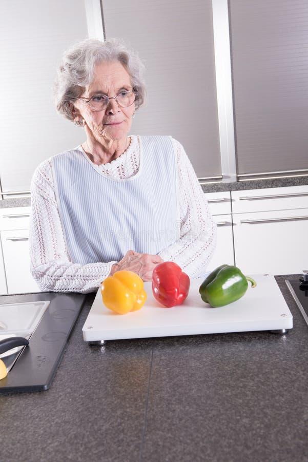 Aktiv kvinnlig pensionär som förbereder paprika royaltyfria bilder