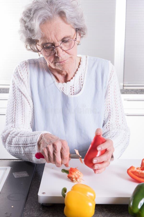 Aktiv kvinnlig pensionär som förbereder paprika royaltyfri bild