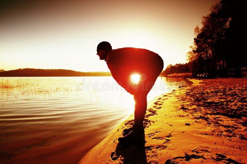 Aktiv manspring för sport och öva på stranden på solnedgången royaltyfria bilder