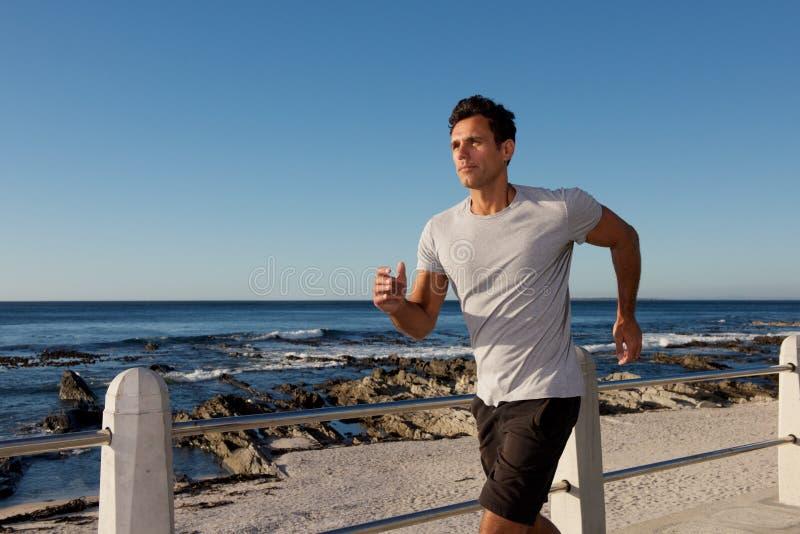 Aktiv mellersta ålderman som utanför joggar förbi havet royaltyfri fotografi