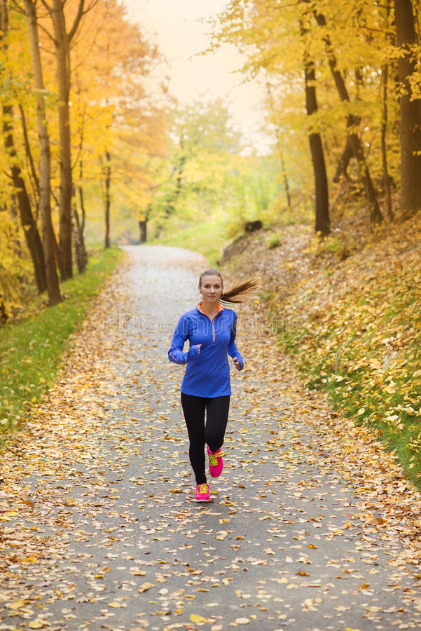 Aktiv och sportig kvinnalöpare i höstnatur royaltyfria bilder