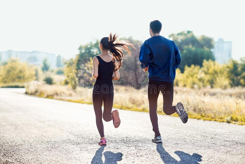 Aktiv sportig kvinna och man som joggar på solig dag fotografering för bildbyråer