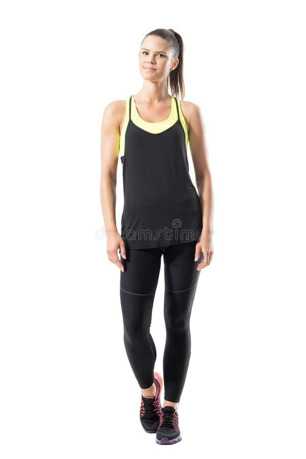 Aktiv sportig ung avkopplad idrottskvinna i den svarta sportswearen som ser kameran arkivbild