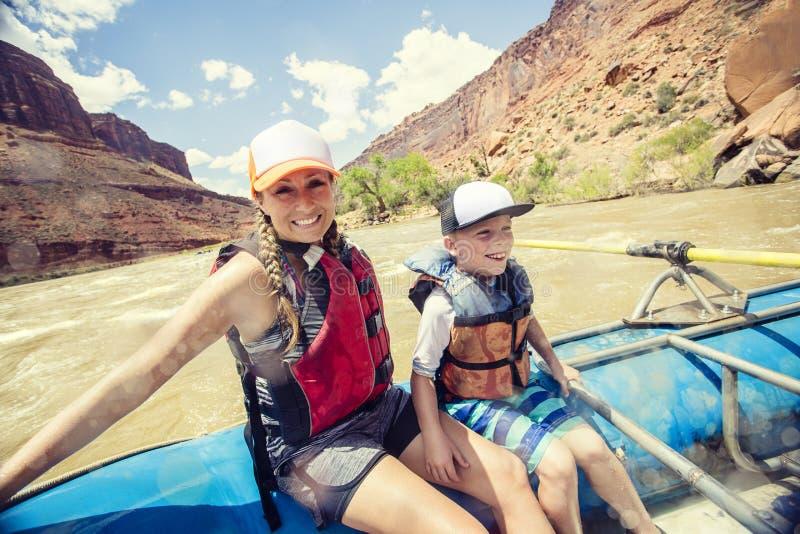Aktiv ung familj som tycker om en rolig tur för rafting för whitewater arkivbild