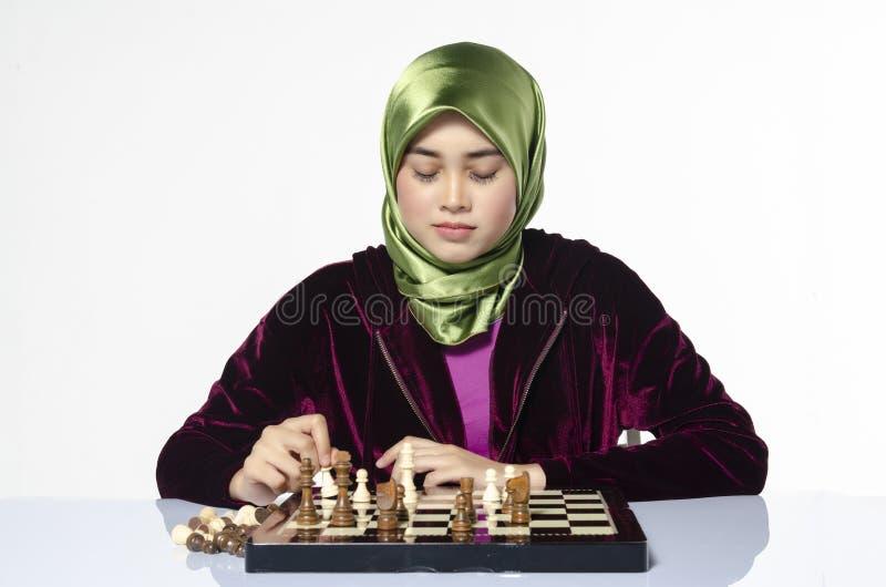 Aktiv ung kvinna som spelar schack över vit bakgrund royaltyfri bild