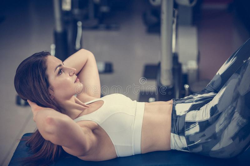 Aktiv ung kvinna som utarbetar hennes abs i idrottshall för konditionklubba royaltyfria foton