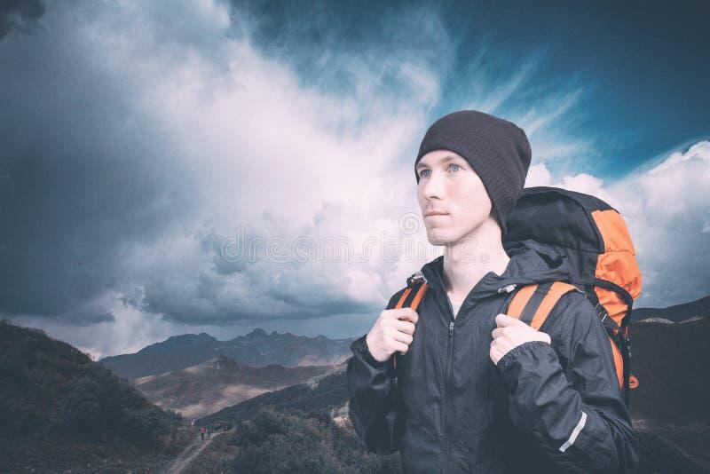 Aktiv ung man som fotvandrar i berget, sidosikt p? molnig landskapbakgrund aktiv livsstil och turism fotografering för bildbyråer