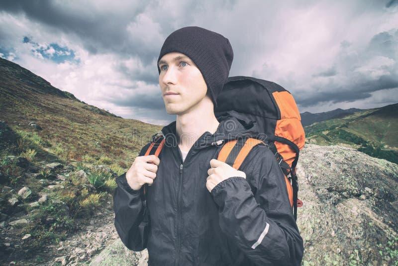 Aktiv ung man som fotvandrar i berget, sidosikt p? molnig landskapbakgrund aktiv livsstil och turism arkivbilder