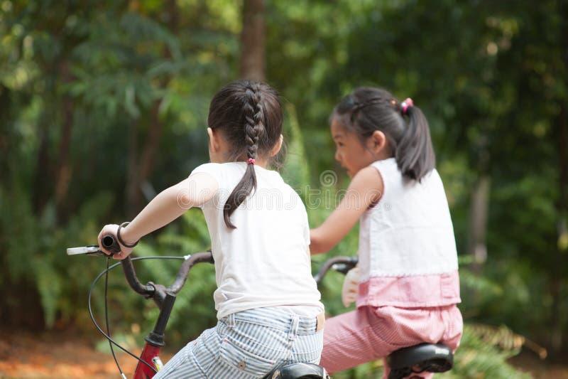Aktiva asiatiska barn som rider den utomhus- cykeln royaltyfria foton