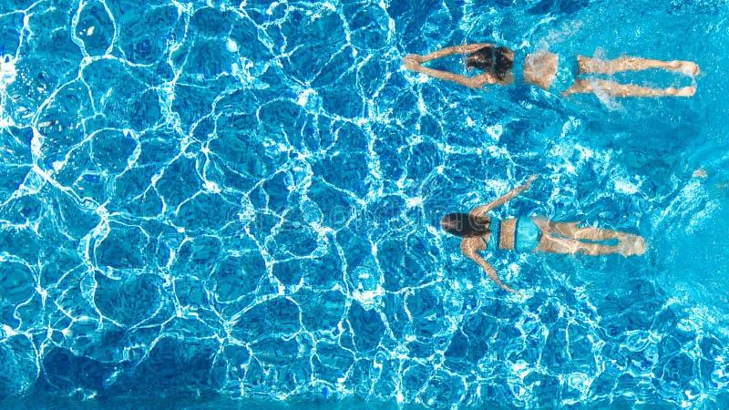 Aktiva flickor i sikt för surr för simbassängvatten flyg- från över, barn simmar, ungar har gyckel på tropisk familjsemester royaltyfri foto