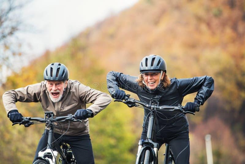 Aktiva höga par med electrobikes som utomhus cyklar på en väg i natur royaltyfria bilder