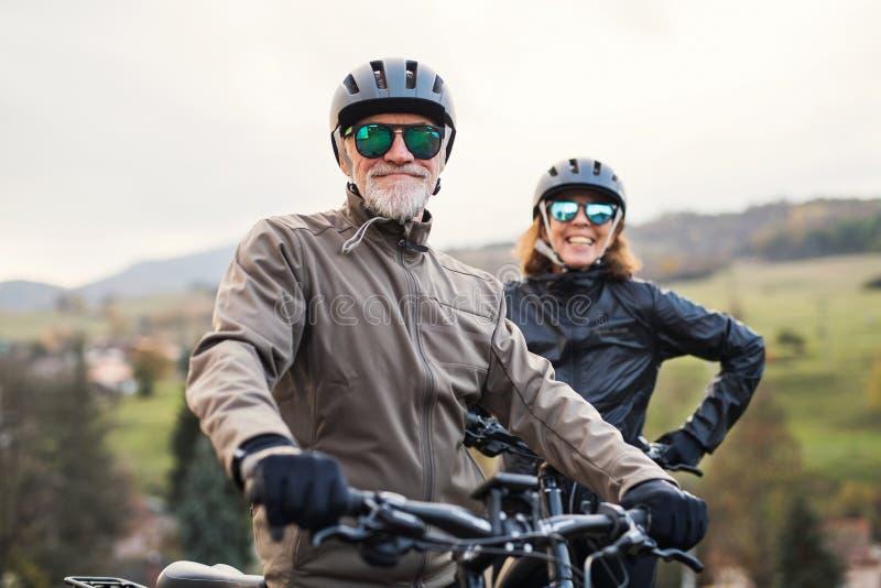 Aktiva höga par med electrobikes som utomhus står på en väg i natur royaltyfri foto