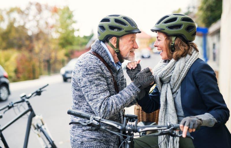 Aktiva höga par som är förälskade med electrobikes som utomhus står på en väg i stad royaltyfri bild