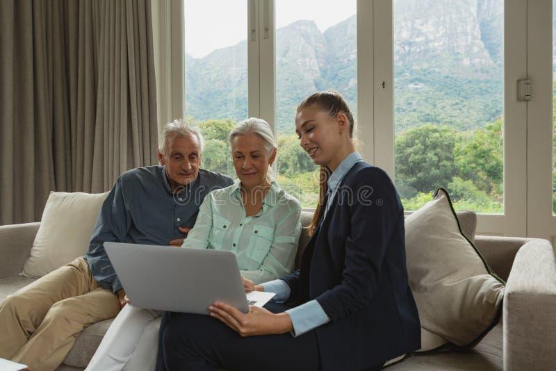 Aktiva höga par som diskuterar med fastighetsmäklaren över bärbara datorn i vardagsrum royaltyfri foto