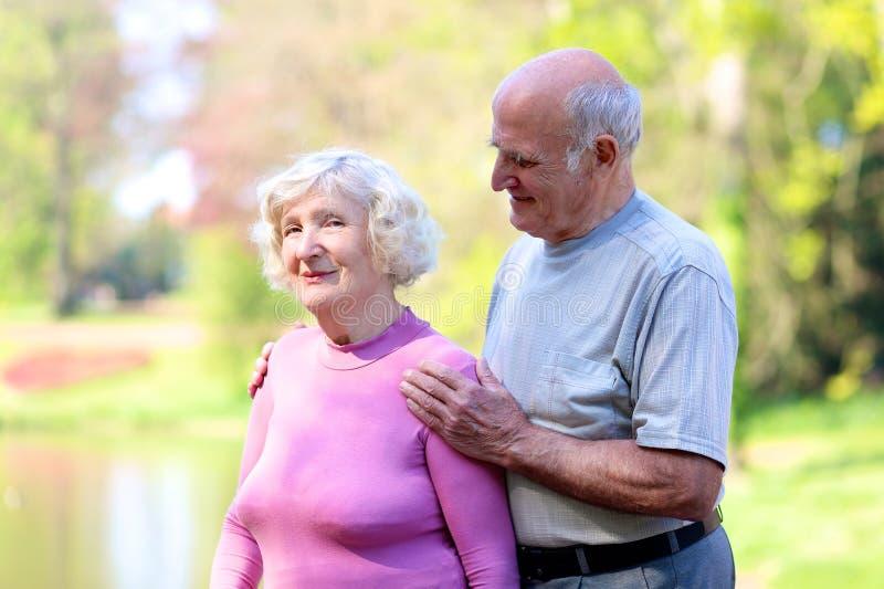 Aktiva höga par som kopplar av i parkera royaltyfria bilder