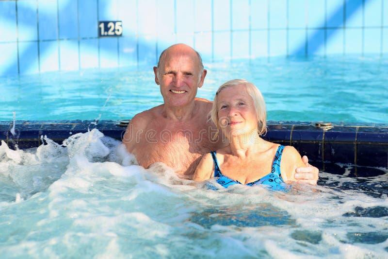 Aktiva höga par som tycker om bubbelpoolen arkivfoton