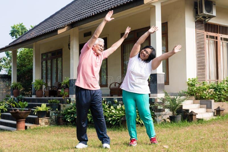 Aktiva höga par som utomhus övar med lyftta armar royaltyfria bilder