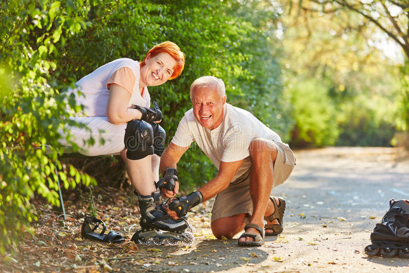 Aktiva inline åka skridskor par i parkera arkivbilder
