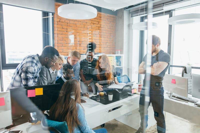 Aktiva kontorsarbetare har samlat runt om en tabell gör forskning fotografering för bildbyråer