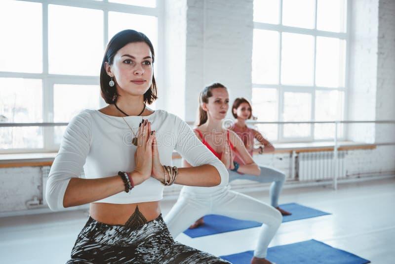 Aktiva kvinnlig som tillsammans gör yogaövningar på grupp Gruppen av övande yoga för vuxen kvinna poserar royaltyfri foto