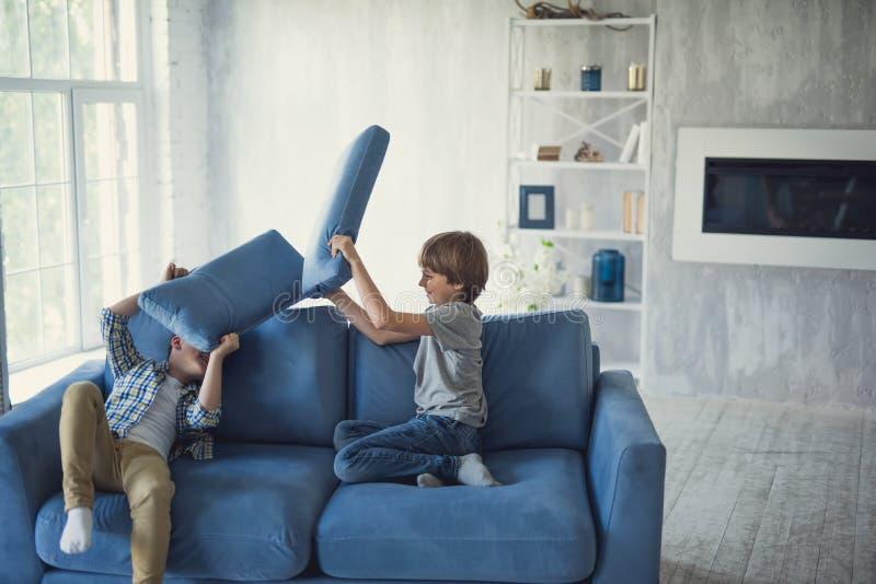 Aktiva pojkar som har gyckel, medan sitta på soffan och slåss royaltyfria foton