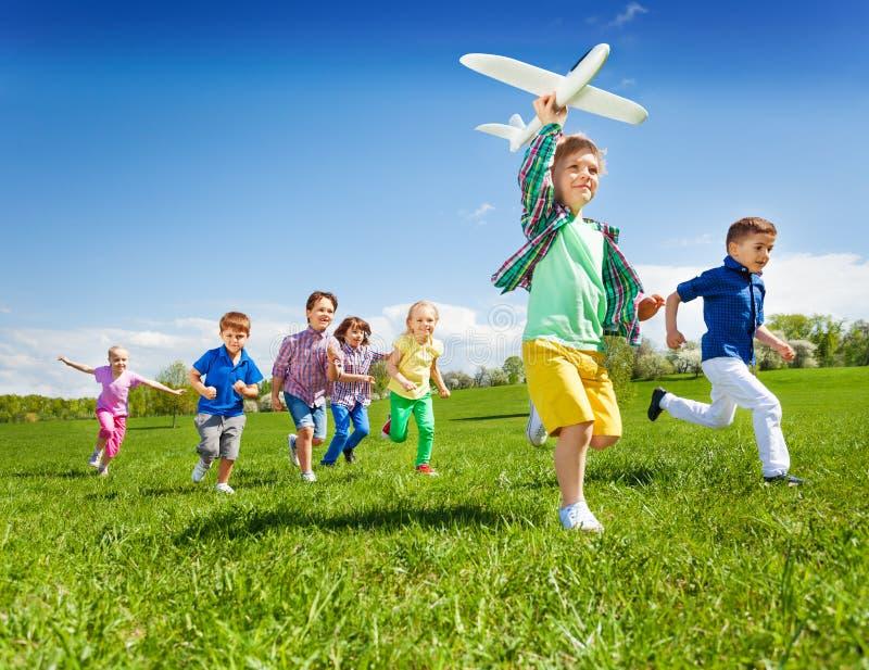 Aktiva springungar med den hållande flygplanleksaken för pojke royaltyfri fotografi