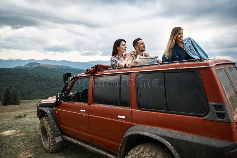 Aktiva unga vänner som använder loppöversikten i bergen royaltyfri foto