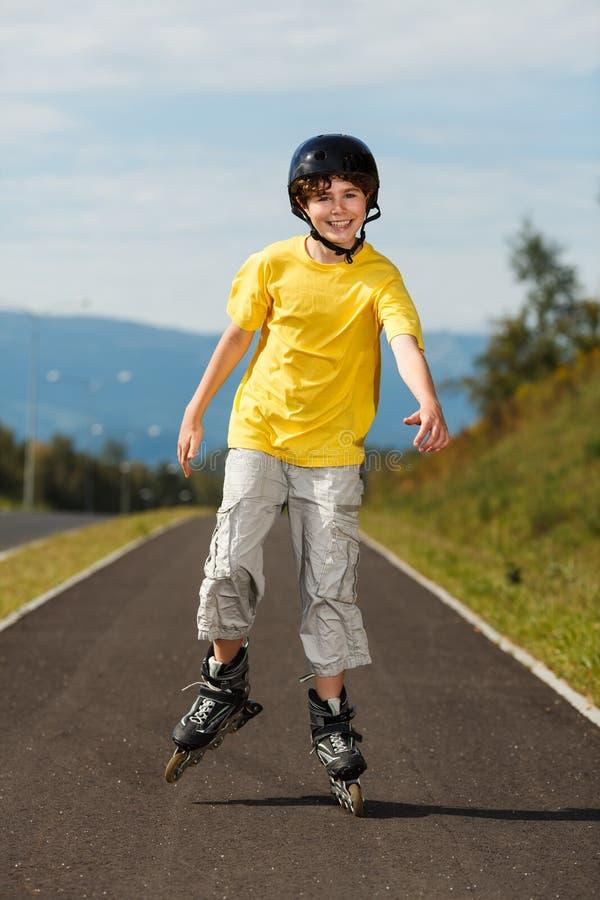Aktiva ungdomar- rollerblading som skateboarding fotografering för bildbyråer